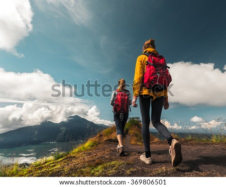 Two ladies hikers walking on the path on top of the mountain - stock photo