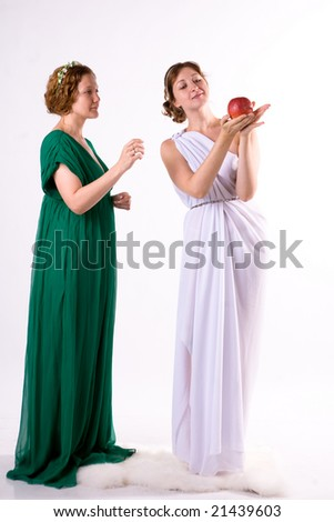 Two ladies in antique dress and one apple on white background - stock photo