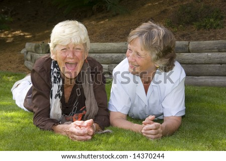 Two ladies laughing together. Best friends for fifty five years. - stock photo
