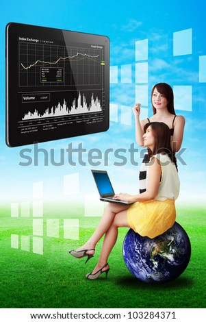 Two lady look at the graph report on touch pad : Elements of this image furnished by NASA - stock photo