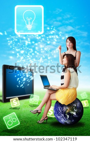 Two lady look at the Light bulb icon from tablet computer : Elements of this image furnished by NASA - stock photo