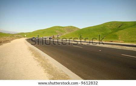 Two lane highway panorama in the midst of country farmland - stock photo