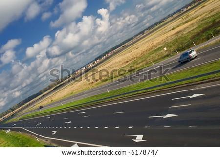 two lane motorway under cloudy sky (tilt view) - stock photo