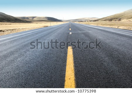 Two lane open road under a blue sky
