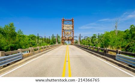 Two lane rural highway along Highway Ninety in Louisiana with vintage bridge ahead. - stock photo