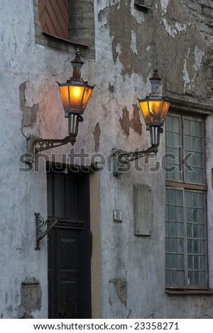two lanterns on an old building - stock photo