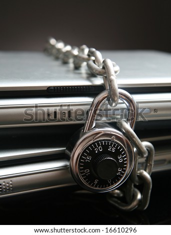 Two laptop computers with chain and combination lock - stock photo