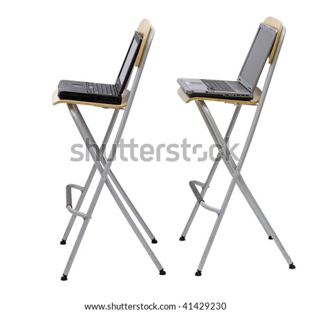two laptops standing on bar high chairs one for second, black and silver one. White background - stock photo