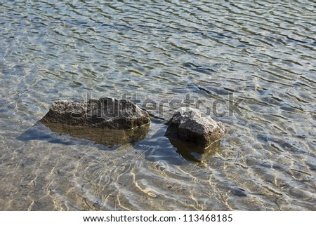 Two large gray rocks in a mountain lake with sunny ripple patterns