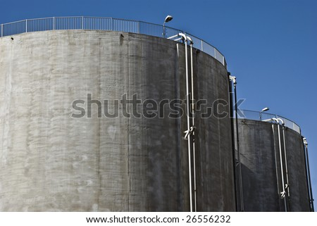 Two large round receptacles for storing industrial liquids or gases. - stock photo