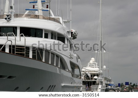 Two large white yachts tied up at a dock
