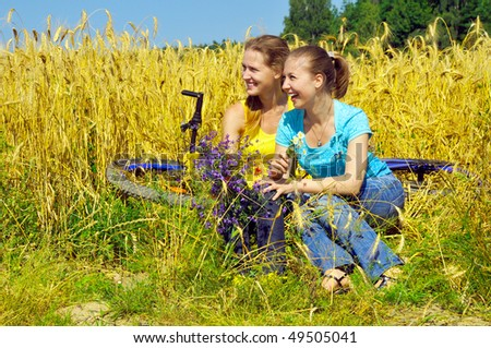 Two laughing beautiful girls rest in golden field