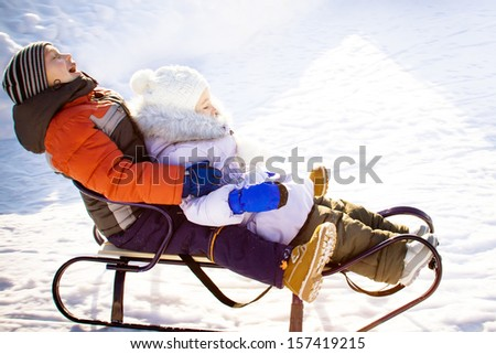 Two laughing kids are sledding  - stock photo