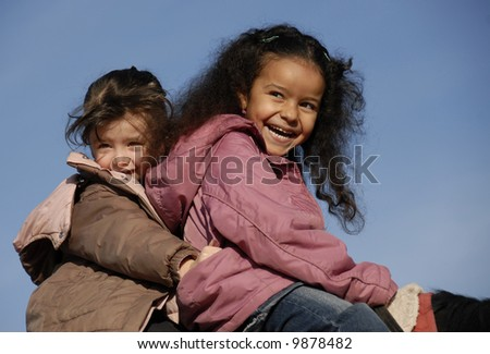 two laughing little girls on a horse : the best friends