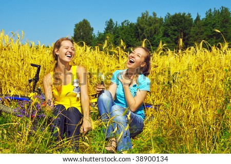 Two laughing pretty girls rest in golden field