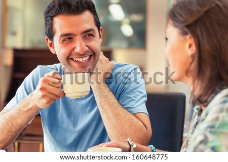 Two laughing students having a cup of coffee in college canteen - stock photo