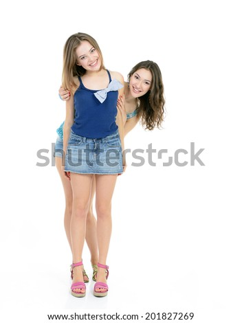 Two laughing teen girls have fun together, isolated on white  - stock photo