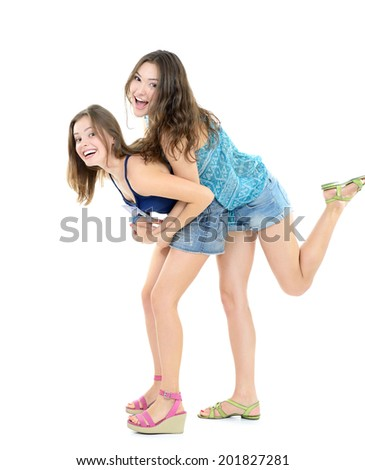 Two laughing teen girls have fun together, isolated on white