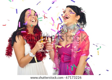 Two laughing women at party celebrating with champagne and confetti - stock photo