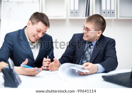 Two laughing young businessmen working together in office