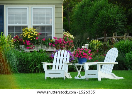 Two lawn chairs in a beautiful garden - stock photo