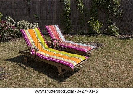 Two lawn chairs on the sun-drenched garden with colorful covers.. - stock photo