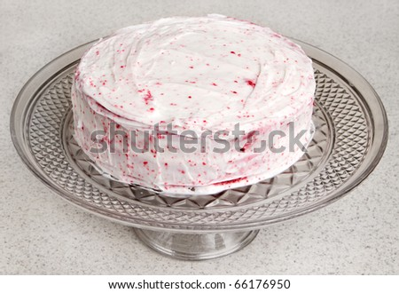 two layer red velvet cake on a glass serving tray - stock photo