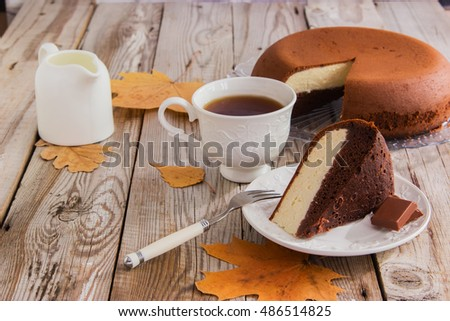 Two layered cake: chocolate and cottage cheese on wooden background with autumn leaves.
