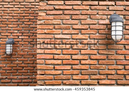 Two layers of old and vintage orange brick wall with white plastic lantern- weathered and worn out in outdoor area - front view - stock photo