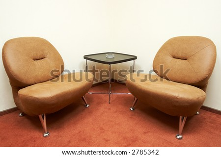 Two leather armchairs and ashtray on a table