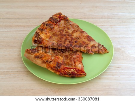 Two leftover cold cheese pizza slices on a green plastic plate atop a wood table top.