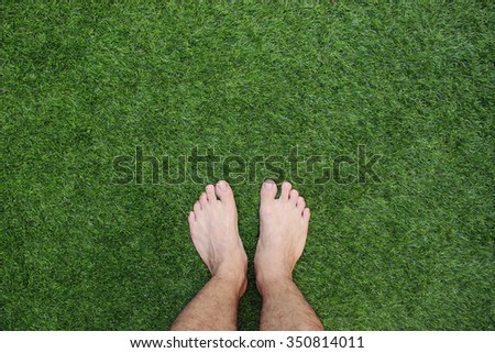 Two legs standing on green grass having fun outdoors in spring park - stock photo