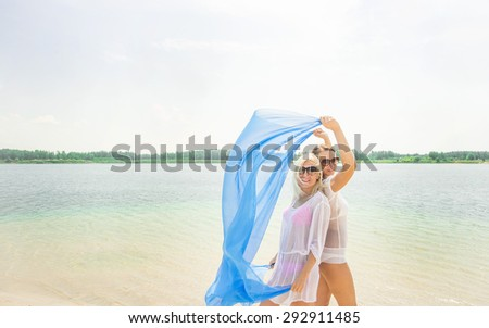 Two lesbian Girls enjoying freedom on the beach sitting with cloth in wind and sun at the sea Homosexual couple of woman together back to back against blue summer sky with clouds background  - stock photo
