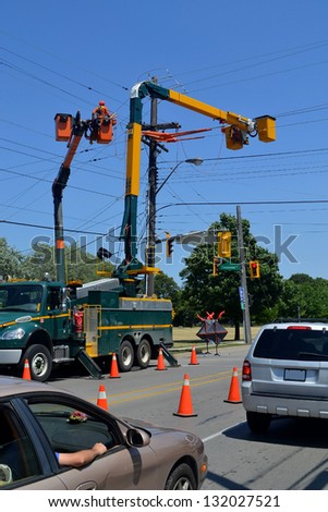 Two lift trucks from a hydro company working on power lines cutting of the traffic in Hamilton Ontario, Canada. - stock photo