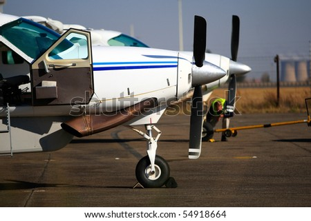 Two light aircraft standing next to each other on the runway - stock photo