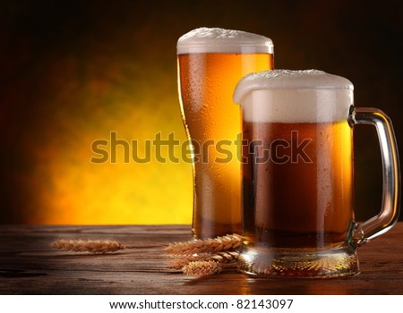 Two light beer glasses with barley spikelets on the dark yellow background.