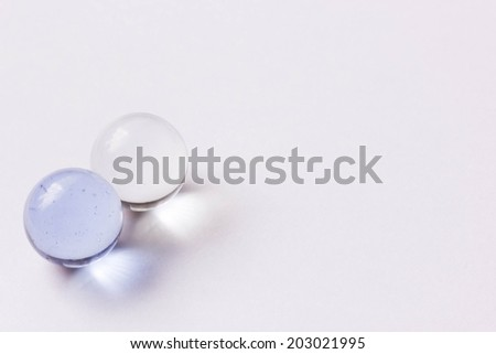 Two light blue and clear glass marbles - Lower left - stock photo