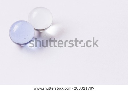 Two light blue and clear glass marbles - Upper left - stock photo