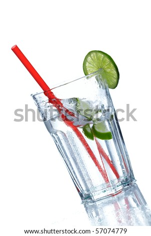 Two lime slices falls into a glass of ice cold soda - stock photo