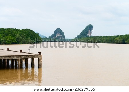 Two limestone cliffs above tropical river and mangrove. Krabi landmark Khao Kanab Nam cliff, Krabi Town, Thailand. - stock photo
