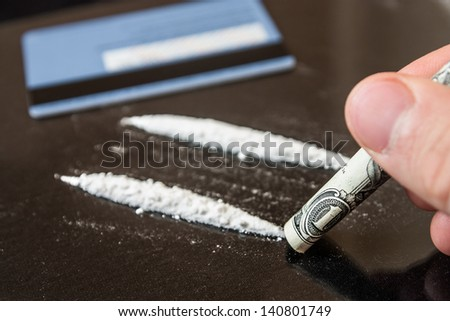 Two line of cocaine beside a wrapped up dollar bill, credit card
