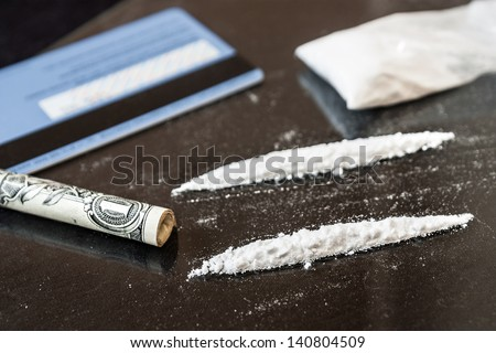 Two line of cocaine beside a wrapped up dollar bill, credit card - stock photo