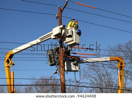 Two lineman working to restore power on electrical lines. - stock photo
