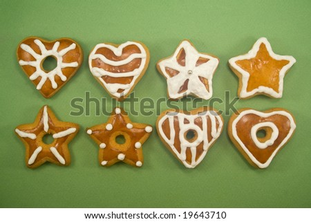 Two lines of star and heart shaped gingerbread cookies against green background - stock photo