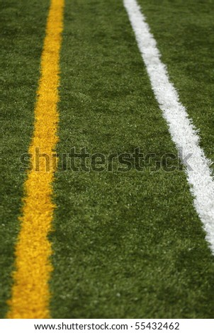 Two lines, yellow and white, on the sideline of a football field. - stock photo