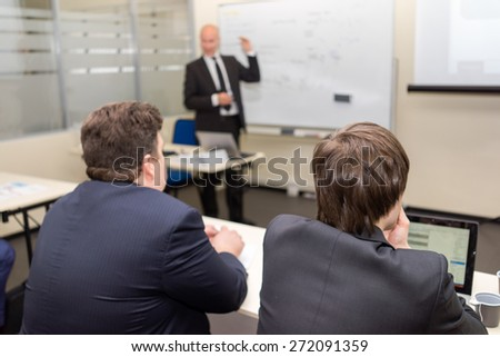 Two listeners sitting in the class and the coach near the desk - stock photo