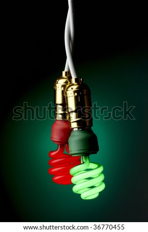Two lit compact fluorescent bulbs (one green, one red) hanging from sockets