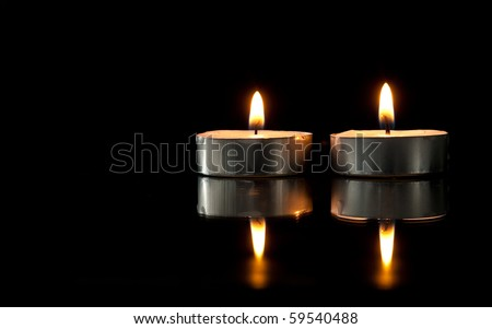 Two Lit Tea Candles with Reflection on Black
