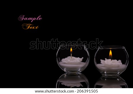 Two Lit White Candles Isolated on a Black Background.Copy Space. - stock photo