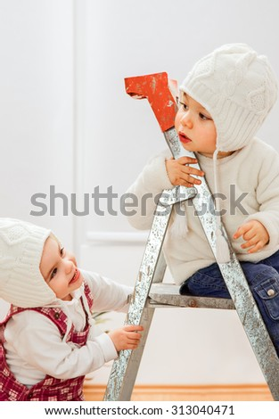 Two litlle kids playing on a ladder in a room of a new apartment.
